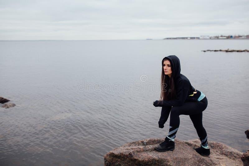 Suporte apto da mulher dos jovens em rochas e resto após um exercício duro foto de stock royalty free
