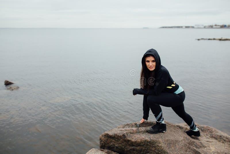 Suporte apto da mulher dos jovens em rochas e resto após um exercício duro imagem de stock