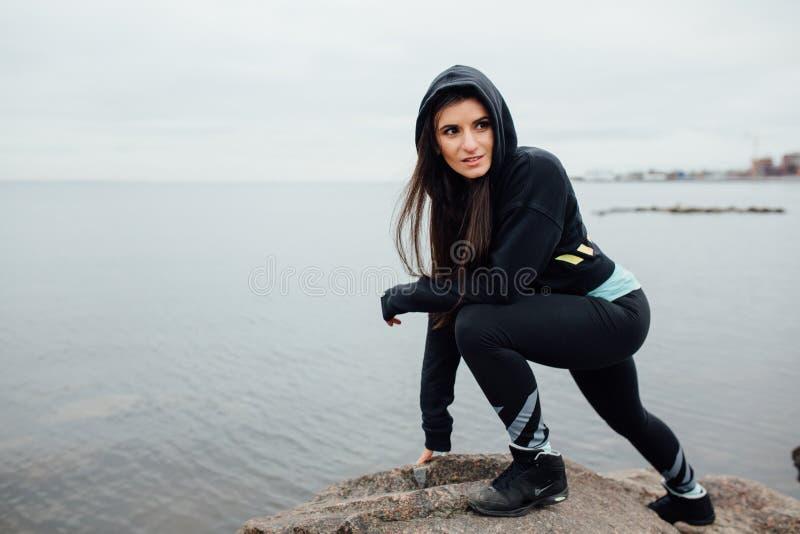 Suporte apto da mulher dos jovens em rochas e resto após um exercício duro imagens de stock royalty free