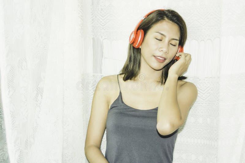 Suporte asi?tico bonito da menina que escuta a m?sica pela janela do quarto, manh? com luz solar macia, com conceito do abrandame imagem de stock