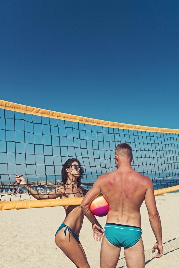 Suporte ativo desportivo novo dos pares perto do jogo do jogo da rede do voleibol no dia de verão Os pares têm o divertimento que fotografia de stock