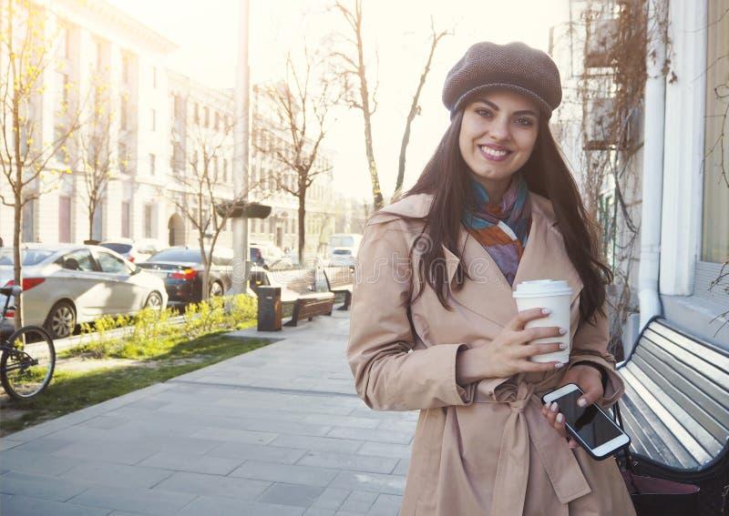Suporte bonito da menina na rua com a xícara de café pelo revestimento e pelo tampão vestindo de trincheira do café fotos de stock royalty free