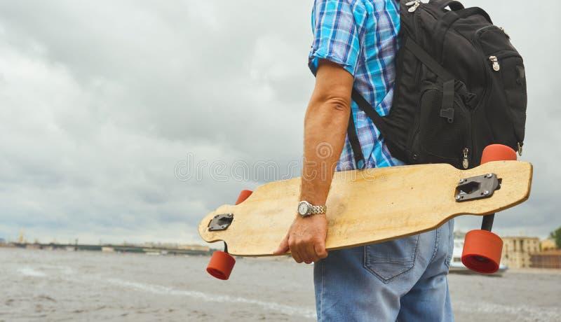 Suporte considerável do indivíduo do moderno com o longboard sobre o fundo do rio da cidade imagens de stock