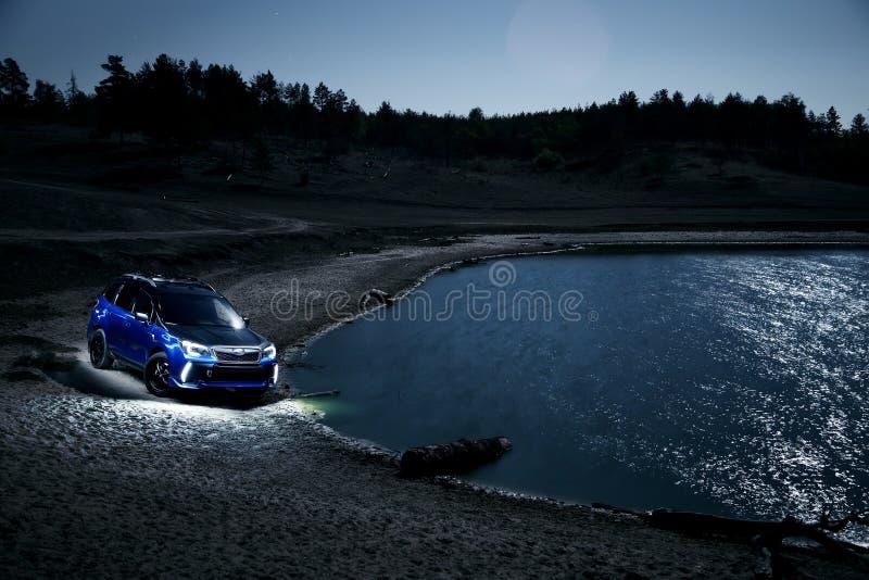 Suporte da guarda florestal de Subaru do carro no campo fora de estrada na noite imagem de stock