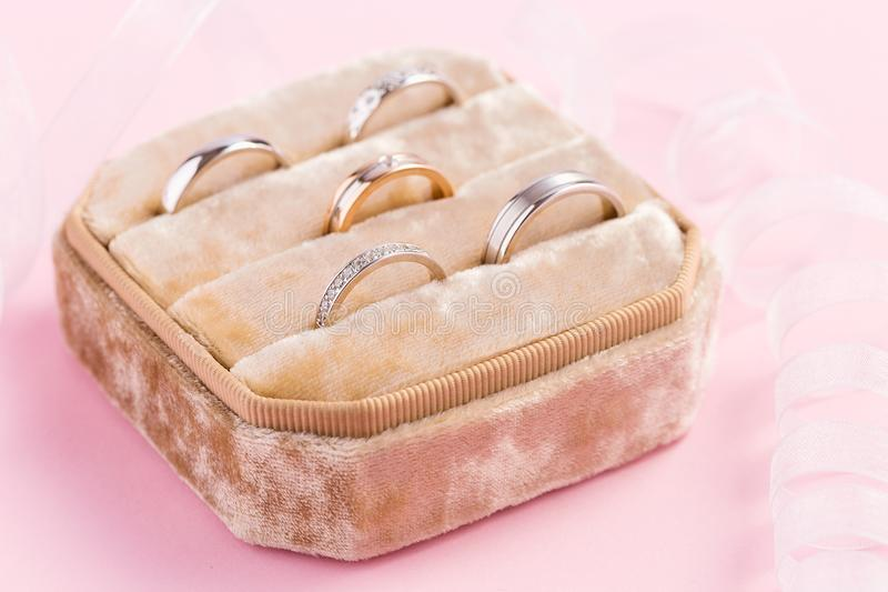 Suporte da joia de veludo com anéis no fundo cor-de-rosa foto de stock royalty free