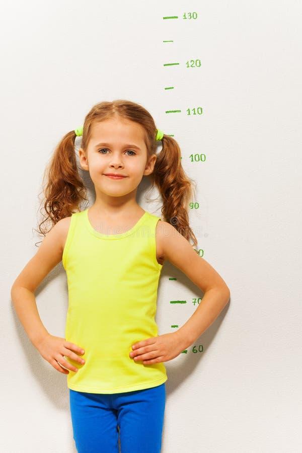 Suporte da menina medindo a escala da altura fotografia de stock