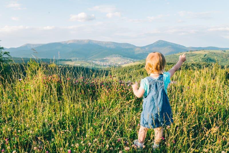 Suporte da menina no pico e vista em montanhas fotografia de stock