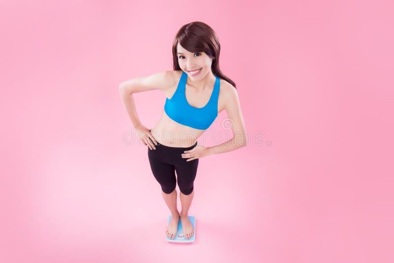 Suporte da mulher na escala do peso imagens de stock