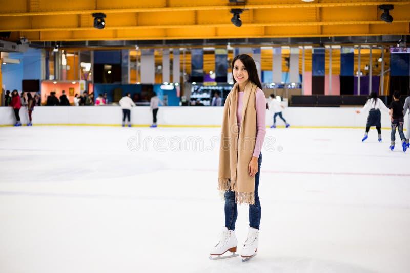 Suporte da mulher na pista de gelo fotografia de stock
