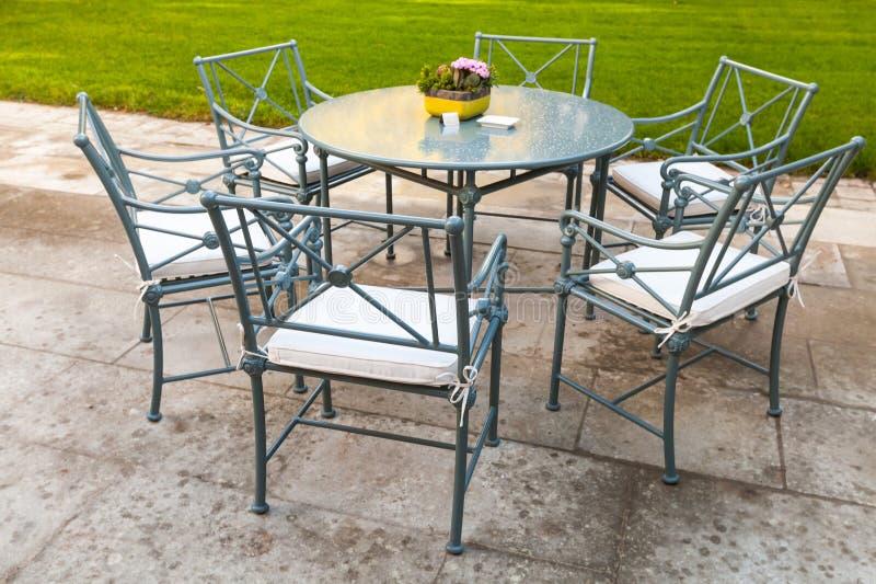 Suporte das cadeiras do metal em torno da mesa redonda fotografia de stock
