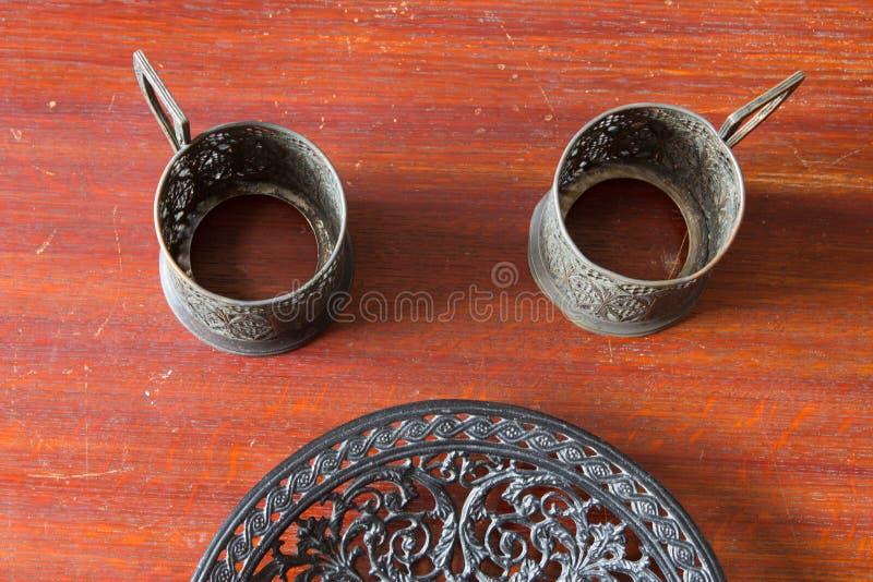 Suporte de copo velho do metal dois e placa a céu aberto do ferro fundido Casa velha imagem de stock royalty free