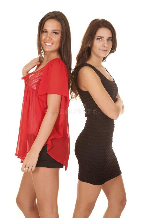 Suporte de duas mulheres no sorriso dos vestidos fotos de stock