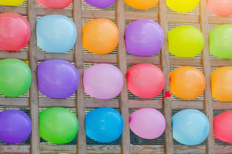 Suporte de madeira com a corda colorida e os balões Fundo colorido colorido do sumário do balão Jogo do divertimento imagens de stock