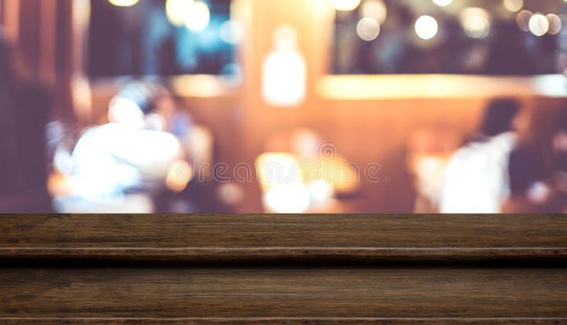 Suporte de madeira escuro do alimento do tampo da mesa da etapa vazia com o dinni dos povos do borrão fotografia de stock