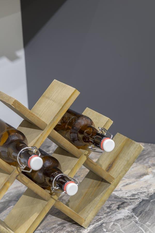Suporte de madeira para garrafas na tabela na cozinha imagem de stock royalty free