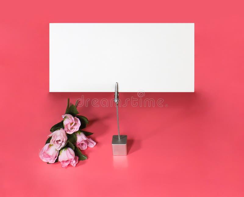 Suporte de nota com rosas e o cartão vazio fotografia de stock