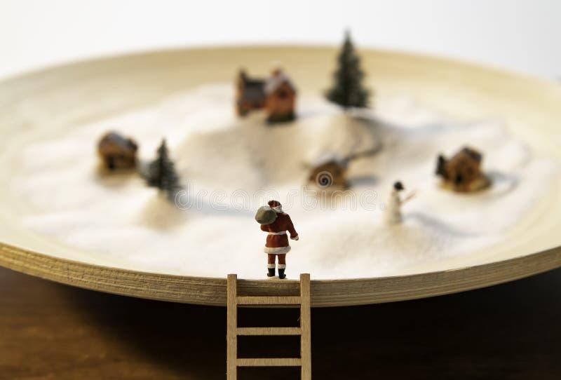 Suporte de Santa na borda da placa de madeira com escada de madeira e da opinião pequena da vila na neve branca imagem de stock