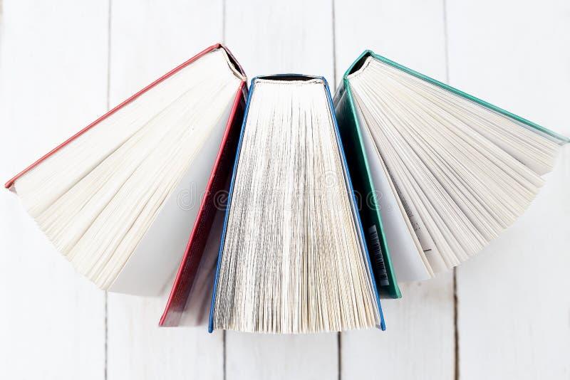 Suporte de três livros aberto em uma tabela de madeira Conceito da instrução imagem de stock royalty free