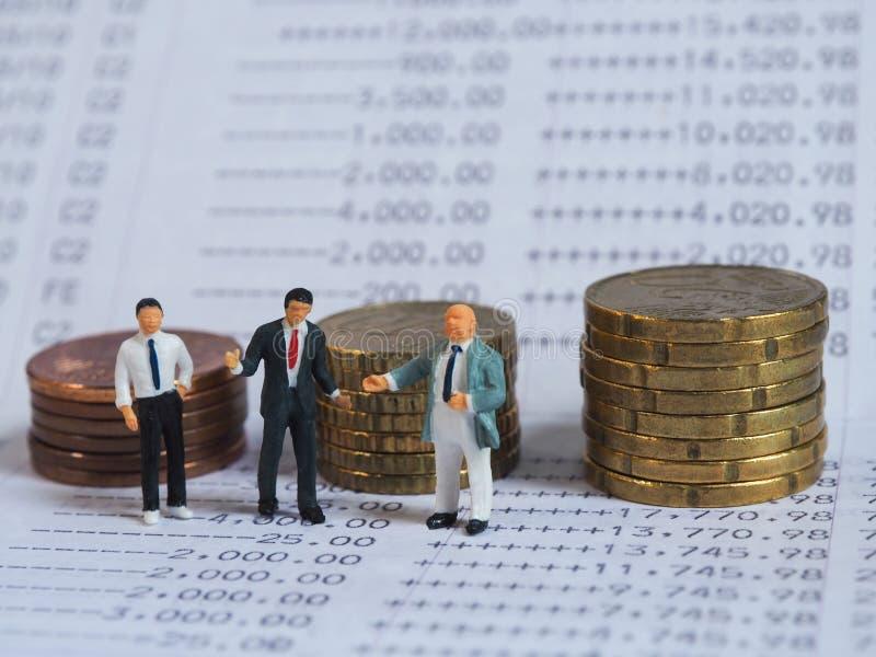 Suporte diminuto do homem de negócios no banco do livro, perto da pilha das moedas Bu imagem de stock