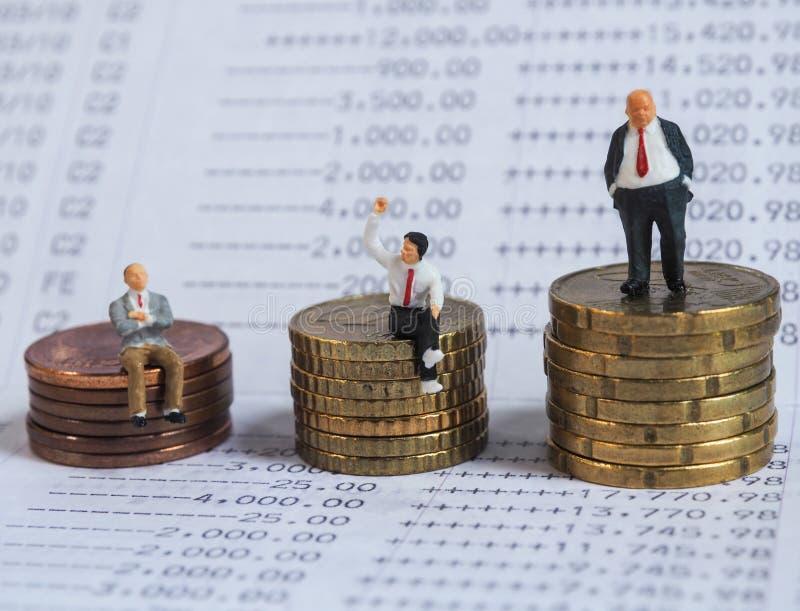 Suporte diminuto do homem de negócios no banco do livro, perto da pilha das moedas Bu imagens de stock royalty free