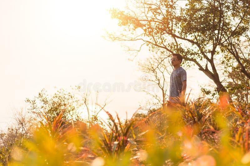 Suporte do homem do curso em horas de verão do penhasco e do por do sol imagens de stock royalty free