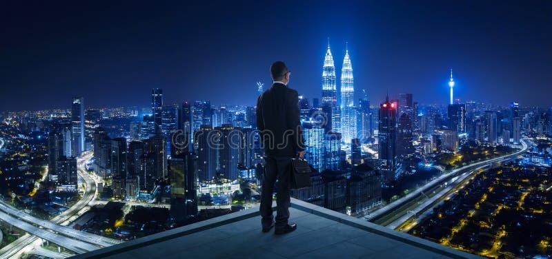 Suporte do homem de negócios no telhado que olha a grande opinião da arquitetura da cidade foto de stock royalty free