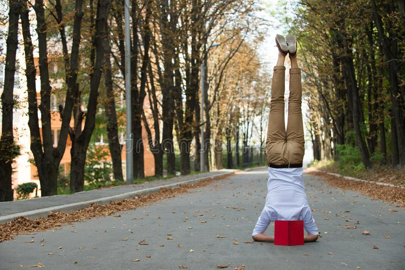 Suporte do homem na cabeça na estrada do parque Estudante com o livro de cabeça para baixo no outono exterior Trabalhe o balanço  imagem de stock royalty free