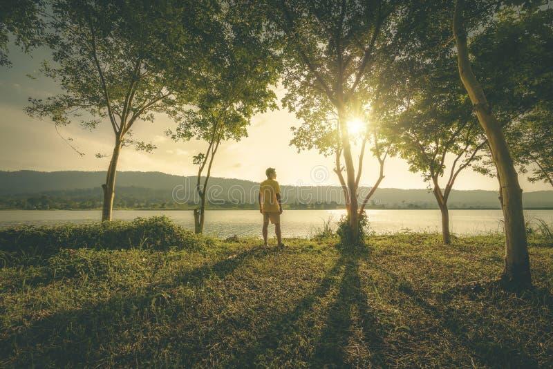Suporte do homem na floresta e perto da água com montanha para trás fotos de stock