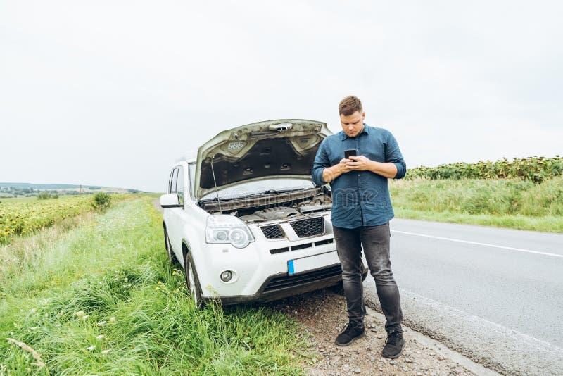 Suporte do homem na frente de carro quebrado fotografia de stock