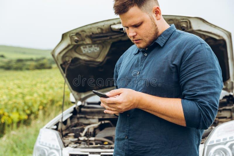 Suporte do homem na frente de carro quebrado fotografia de stock royalty free