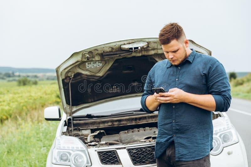 Suporte do homem na frente de carro quebrado foto de stock