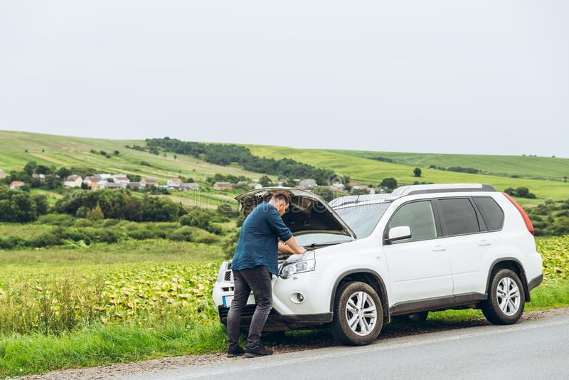 Suporte do homem perto de carro quebrado com capa aberta Serviço de urgências foto de stock royalty free