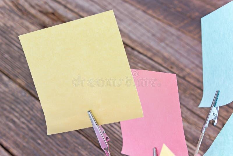 Suporte do memorando com notas pegajosas coloridas no fundo de madeira fotografia de stock