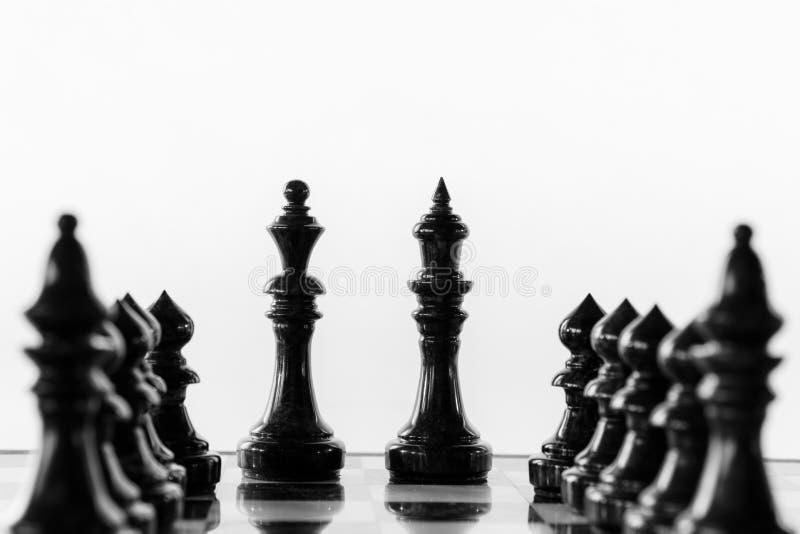 Suporte do rei e da rainha da xadrez em um tabuleiro de xadrez entre fileiras dos penhores fotos de stock royalty free