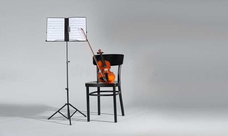 Suporte do violino, da cadeira e da nota com as folhas de música no fundo cinzento imagens de stock royalty free