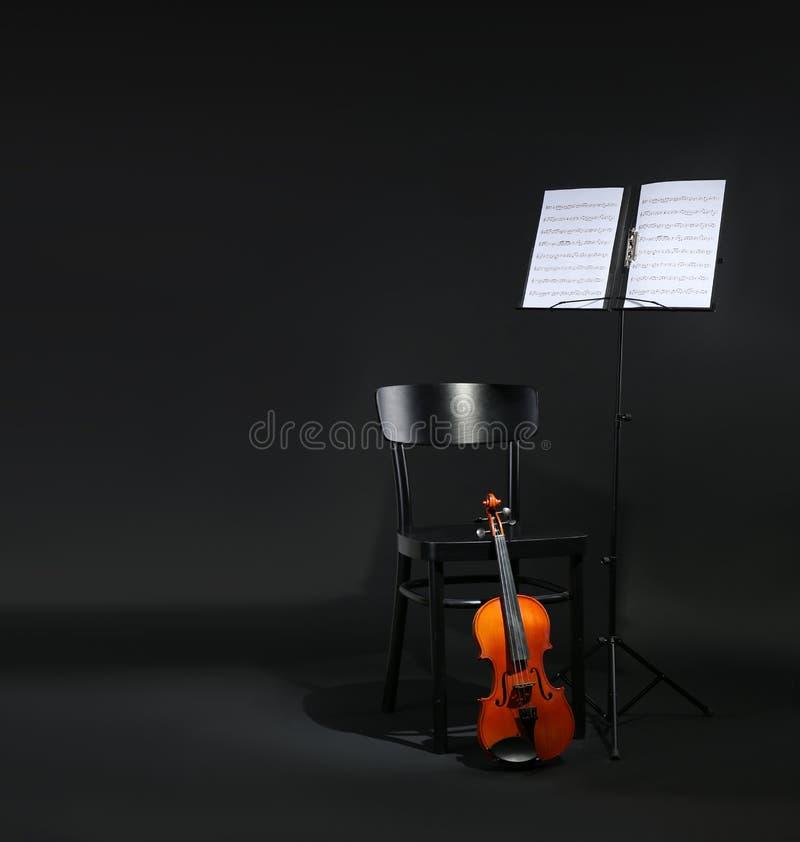Suporte do violino, da cadeira e da nota com as folhas de música no fundo preto fotografia de stock royalty free