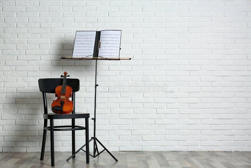 Suporte do violino, da cadeira e da nota com as folhas de música perto da parede de tijolo fotografia de stock