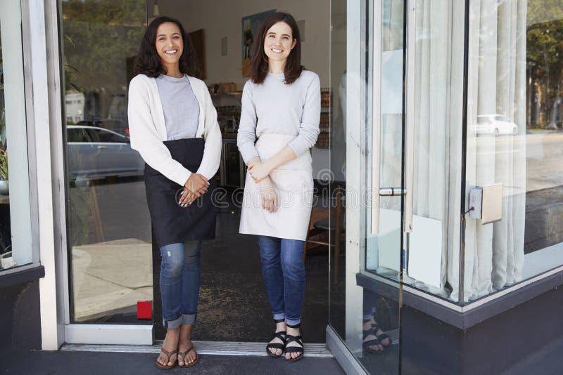 Suporte fêmea de dois proprietários empresariais fora de sua cafetaria imagens de stock