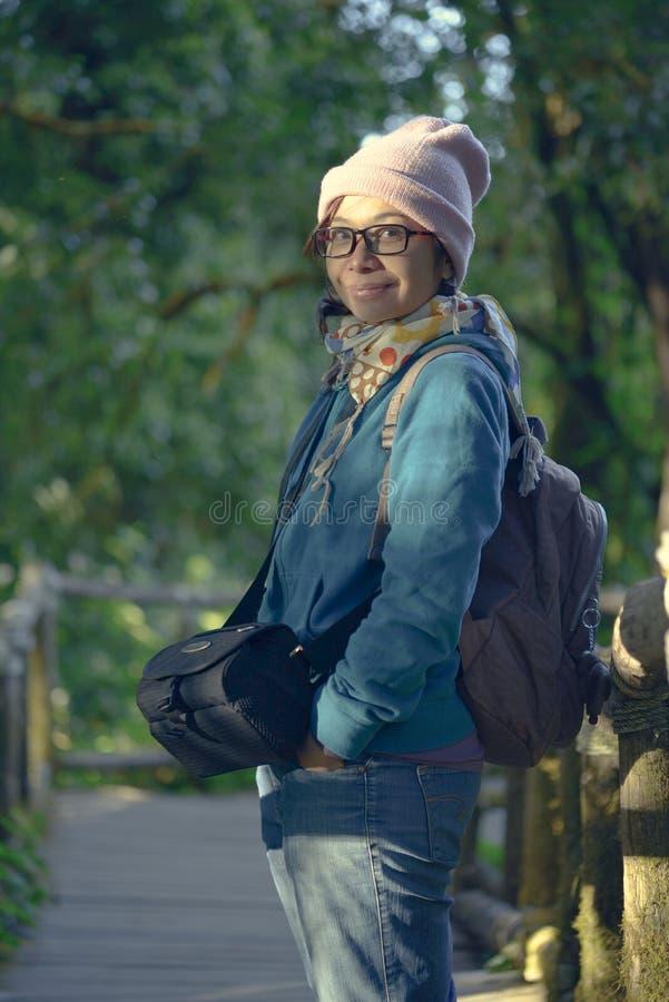 Suporte fêmea dos turistas em uma passagem de madeira fotografia de stock royalty free