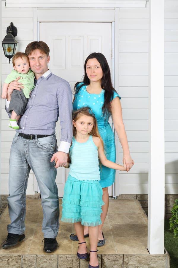 Suporte feliz da família de quatro pessoas no patamar da casa branca nova. imagens de stock