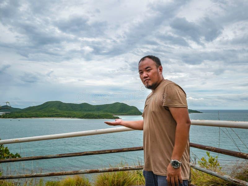 Suporte gordo asiático do viajante no ponto de vista com o oceano idílico tropical e o céu branco da nuvem no tempo de férias imagens de stock