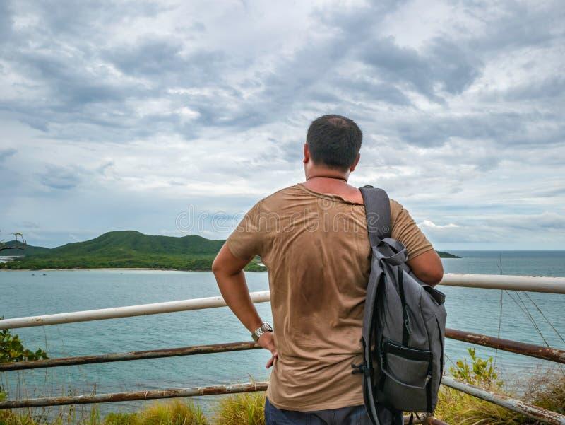 Suporte gordo asiático do viajante no ponto de vista com o oceano idílico tropical e o céu branco da nuvem no tempo de férias fotos de stock