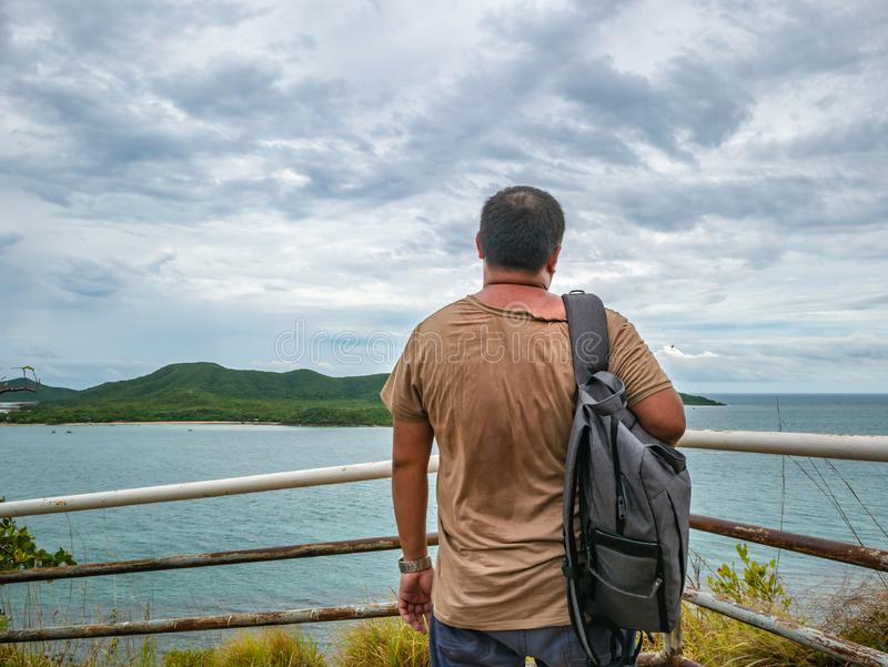 Suporte gordo asiático do viajante no ponto de vista com o oceano idílico tropical e o céu branco da nuvem no tempo de férias fotografia de stock