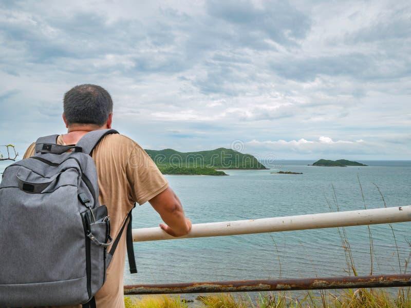Suporte gordo asiático do viajante no ponto de vista com o oceano idílico tropical e o céu branco da nuvem no tempo de férias imagem de stock royalty free