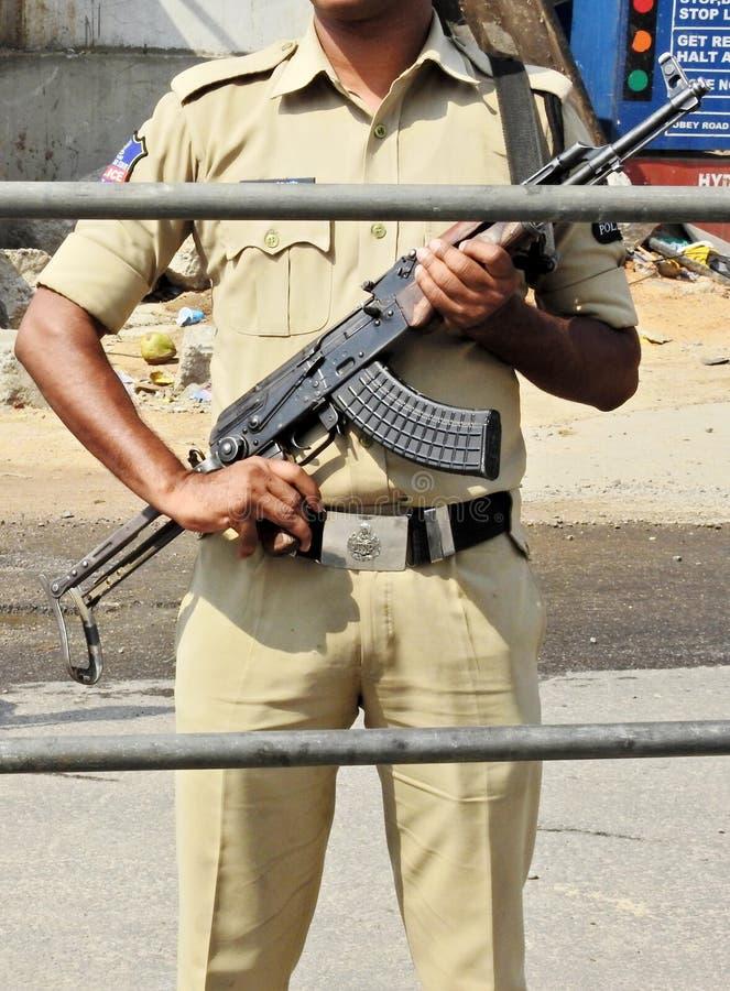 Suporte indiano do homem da pol?cia com a arma atr?s da barricada na estrada foto de stock royalty free