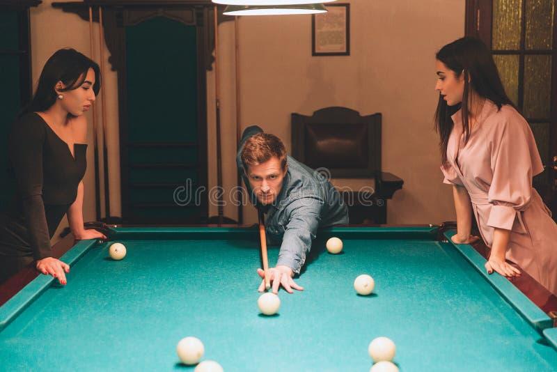 Suporte novo do jogador do ruivo entre dois modelos Aponta na bola de bilhar As jovens mulheres estão e olham o gamel Inclinam-se imagem de stock royalty free