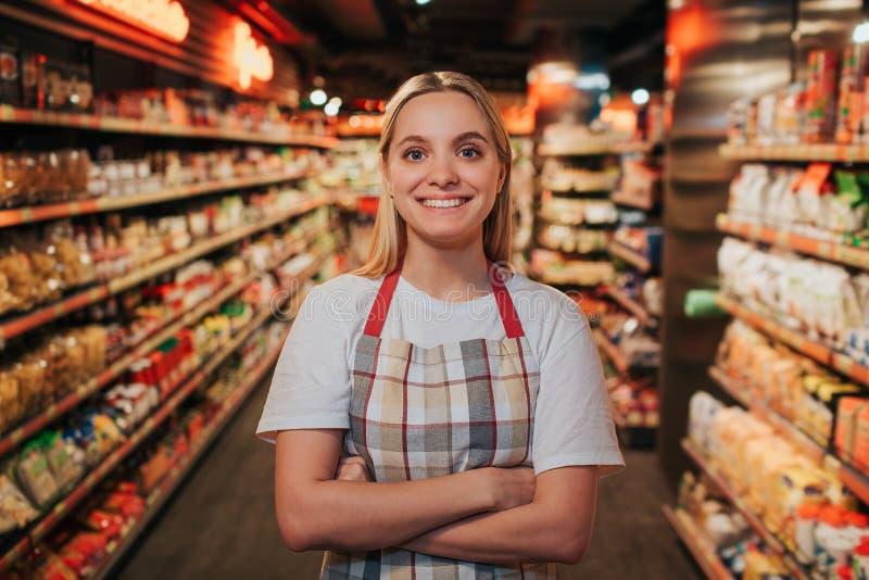 Suporte ocupado da jovem mulher na linha entre shelfs com massa Levanta na câmera e no sorriso Modelo positivo feliz foto de stock royalty free