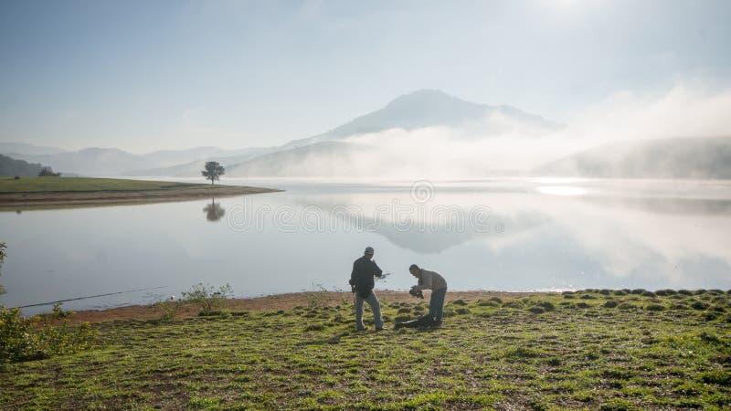 Suporte pela árvore sozinha do anh do lago no lago, nascer do sol no mountai, nevoento, nuvem de dois homens no céu fotos de stock royalty free