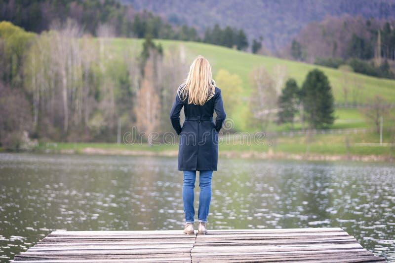 Suporte pensativo da mulher no lago imagens de stock royalty free