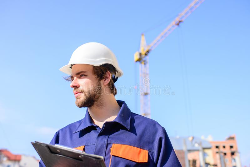 Suporte protetor do capacete do coordenador na frente do fundo do céu azul O capacete do coordenador do construtor trabalha no ca foto de stock
